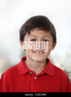 Happy cheerful young Latino or Hispanic boy in red shirt against light background in portrait mode with copy space - Stock Photo
