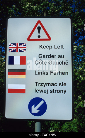 bilingual warning sign for lorry drivers of different nationality's to keep left on road leaving industrial estate - Stock Photo