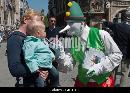 A street performer dressed in clown clothes with a white painted face and long Pinocchio type nose interacts with - Stock Photo