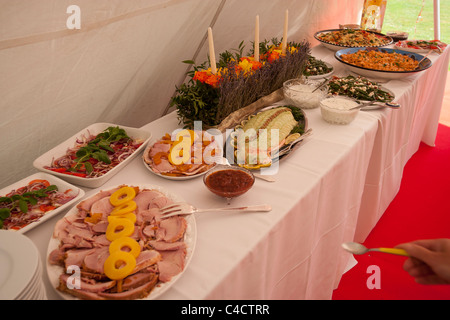 Tables laid out with food for a party in a marquee - Stock Photo