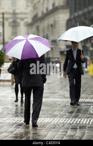 London City workers in rain with umbrellas in Queen Street, London, UK. - Stock Photo