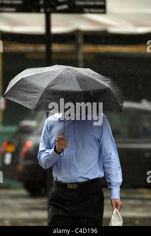 London City worker in rain with umbrella in Queen Street, London, UK. - Stock Photo