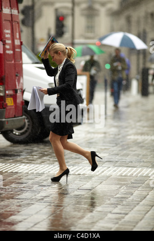 London City worker running in the rain, no umbrella. Queen Street, London, UK. - Stock Photo