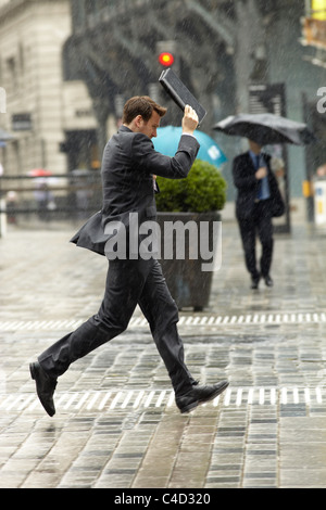 London City worker running in the rain. - Stock Photo