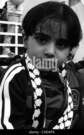 Local Palestinian boy participates on a demonstration in the Palestinian village of Bil'in against the West Bank - Stock Photo