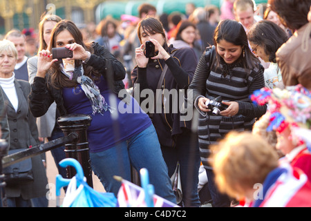 Tourists taking pictures on the Mall the evening before the royal wedding of Prince William and Kate Middleton - Stock Photo