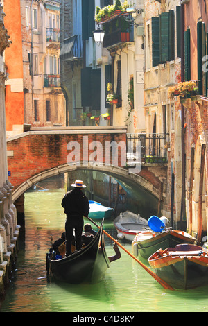 Vertical oriented image of gondola passing on small canal among old historic houses and bridge in Venice, Italy. - Stock Photo