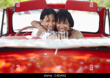 young adult brunette twin women driving convertible red car and looking over shoulders. Horizontal shape, rear view, - Stock Photo