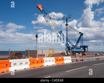 A crawler crane erecting pre-cast concrete sections of a new sea wall at Redcar Cleveland North Yorkshire June 2011 - Stock Photo