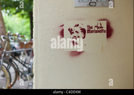 Stencil showing the German politician /  Federal Chancellor Angela Merkel's face with the words The Marionette in - Stock Photo