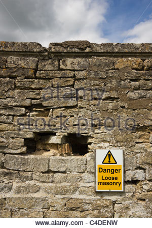 Danger Loose masonry sign on crumbling stone wall, Easton Walled Gardens, Grantham, Lincolnshire, England, UK - Stock Photo