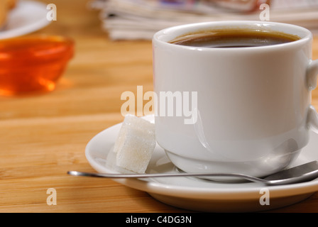 Cup of black coffee on the wooden table with glasses and newspaper aside - Stock Photo