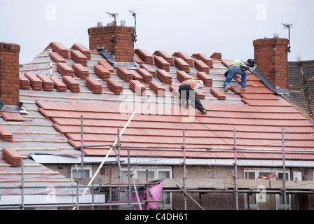 Two Men on Roof of House Laying New Roof Tiles on Three Neighbouring Properties, ACIS Re Roofing, Hastilar Road - Stock Photo
