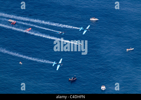 The Extra aerobatic aircraft of the Blades in formation over the sea at Gibraltar - Stock Photo