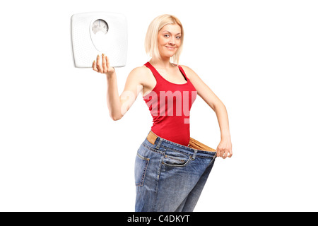 Portrait of a weight loss female holding a weight scale - Stock Photo