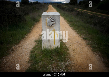 A boundary stone decorated with a shell and a yellow arrow in a track in the French Way that leads to Santiago, - Stock Photo
