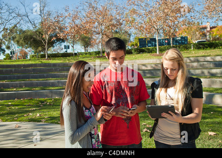 Multi ethnic racial Ethnically diverse group teenagers using iPad iPhone mobile phone Blackfoot American Indian, - Stock Photo