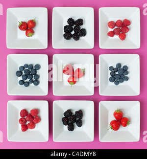 Strawberries, raspberries, blueberries and blackberries in square dishes on a pink background - Stock Photo