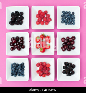 Strawberries, raspberries, blueberries, cherries and blackberries in square dishes on a pink background - Stock Photo