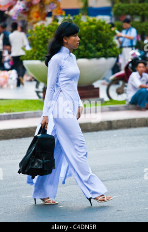 Woman in white Ao Dai crossing the street - Stock Photo