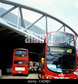 Red double-decker buses pass under Network Rail's new Viaduct Bridge over Borough HIgh Street near Borough Market - Stock Photo