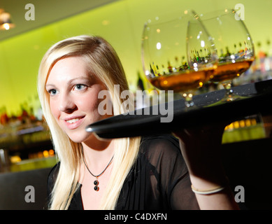 Waitress in a cocktail bar carrying a tray of brandy balloon glasses - Stock Photo