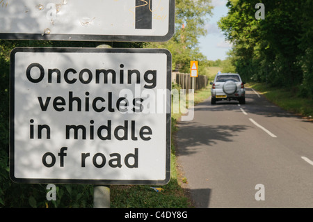 Road sign warning drivers that oncoming vehicles will be in the middle of the road - Stock Photo