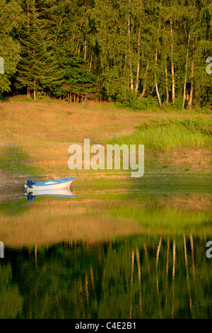 Moored boat at sunset time Lokve lake in Gorski Kotar Croatia countryside tranquillity tranquil unwind spot lakeside - Stock Photo