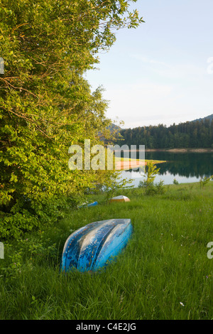Boats laid ashore on the grass,  Lokve lake in Gorski Kotar, Croatia field lakeside Primorje-Gorski Kotar County - Stock Photo