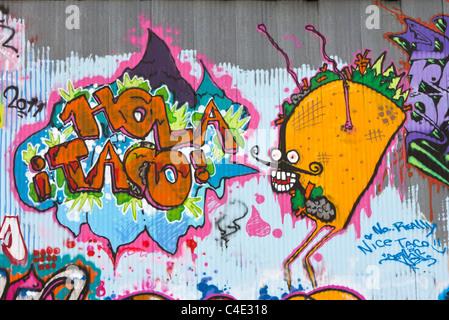 A graffiti mural on corrugated steel depicting a taco caricature - Stock Photo