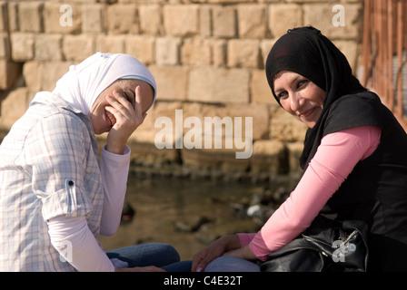 Two young Palestinian women by the Sea Castle, Sidon, Lebanon. - Stock Photo