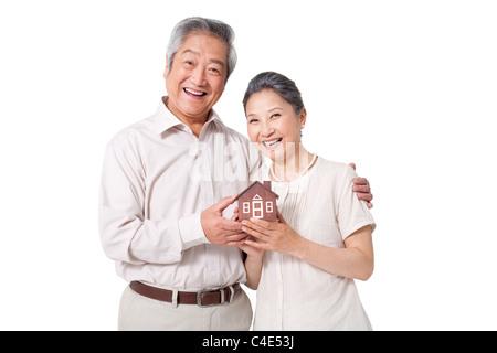 Senior Couple Holding A Model Home - Stock Photo