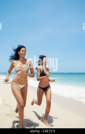 couple of beautiful twins in swimwear running on tropical beach during holidays. Horizontal shape, copy space - Stock Photo