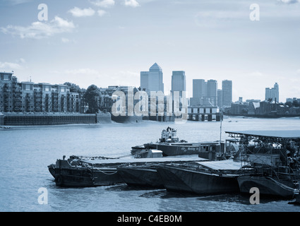 Old moored barges on the River Thames and Canary Wharf on the Horizon, London, UK. - Stock Photo