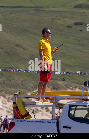 RNLI_ Royal National Lifeboat Institution lifeguard standing on vehicle at Woolacombe Bay Beach, Devon, UK - Stock Photo