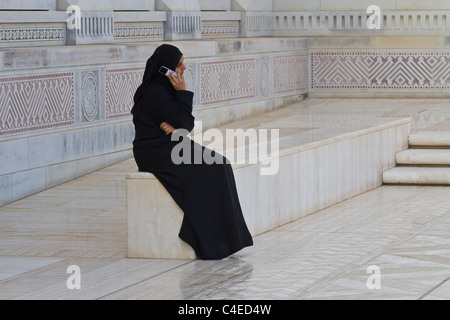 A Mulsim woman talking on a cell phone outside the Grand Mosque in Muscat, Oman. - Stock Photo