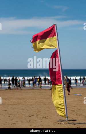 Warning Flag markers on the Blue flag sandy beach, as summer surfers take to the sea in dangerous conditions at - Stock Photo