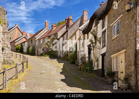Traditional English houses on Gold Hill, Shaftesbury, Dorset, England, UK viewed from bottom of street - Stock Photo