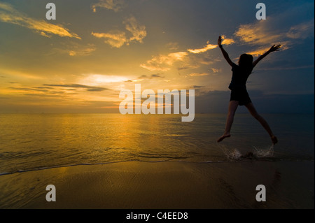 A young jumping for joy and enjoying her freedom on the beach at sunset. Taken on Phra Ae Beach, Koh Lanta, Thailand - Stock Photo