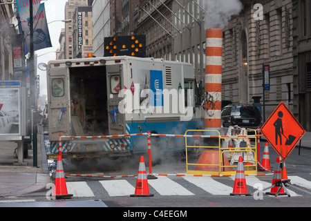 A Con Edison service truck and maintenance crew work at a site on a street in New York City. - Stock Photo