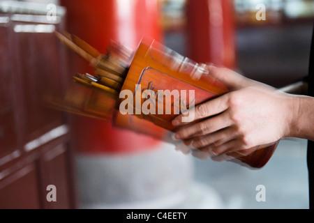 People shaking out fortune sticks at the Taoist temple of Xuen Miao Guan, Suzhou, China. - Stock Photo