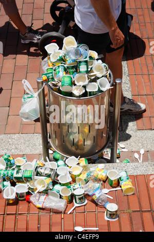 Plastic yoghurt pots in litter bin following free tasting in Street in Spain - Stock Photo