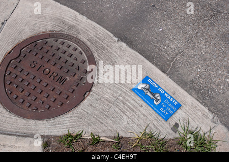 Florida Panhandle Apalachicola storm drainage and sign warning about pollution of the Gulf coastal waters. - Stock Photo