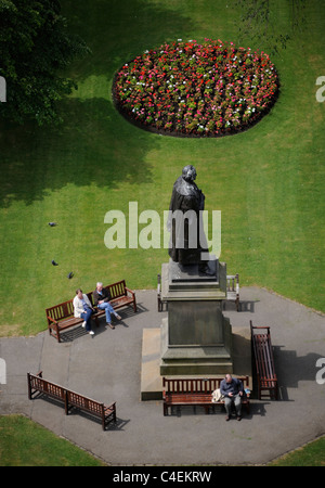 People stop for lunch on the park benches in Princes Street Gardens, Edinburgh, on a sunny afternoon - Stock Photo