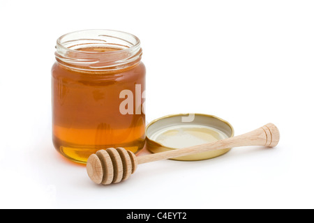 Jar of open honey with drizzler over white - Stock Photo