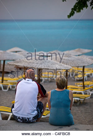 Couple sitting on a Greek beach watching a storm out to sea - Stock Photo