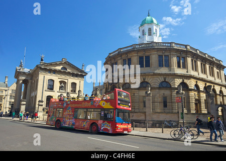 Open-top tourist bus outside Sheldonian Theatre and Clarendon Building, Broad Street, Oxford University, City centre, - Stock Photo