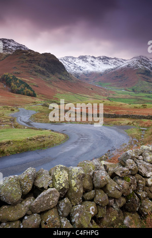 A winding mountain road descends into Great Langdale valley, Lake District National Park, Cumbria, England. - Stock Photo
