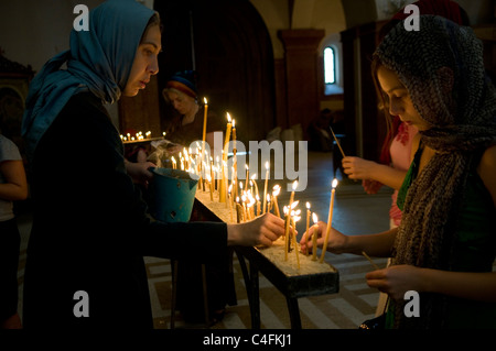 Locals lighting candles The Holy Trinity Cathedral commonly known as The Sameba cathedral in Tbilisi, Republic of - Stock Photo