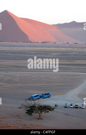 Tourist vehicles at the base of Dune 45, Sossusvlei, Namibia. - Stock Photo